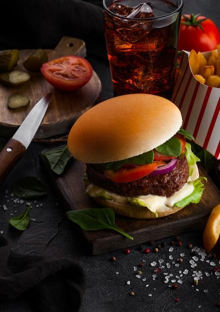 Frischer rindfleischburger mit soße und gemüse und glas cola-erfrischungsgetränk mit kartoffelchips-pommes auf steinküche. Premium Fotos