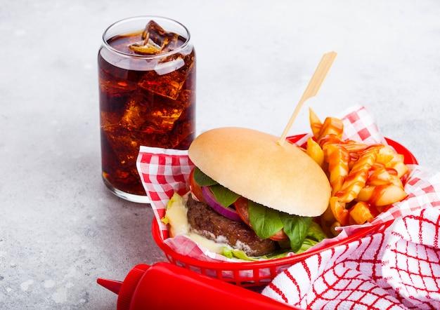Frischer rindfleischburger mit soße und gemüse und glas cola-erfrischungsgetränk mit kartoffelchips-pommes im roten servierkorb auf steinküche. Premium Fotos
