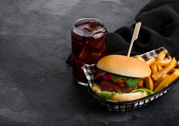 Frischer rindfleischburger mit soße und gemüse und glas cola-erfrischungsgetränk mit kartoffelchips-pommes im schwarzen servierkorb auf steinküche. Premium Fotos
