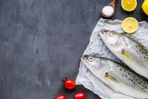 Frischer roher fisch mit gewürzen, zitrone, salz auf dunklem steinhintergrund Premium Fotos