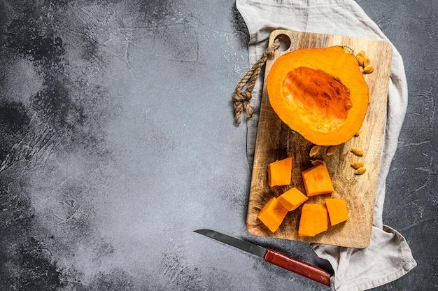 Frischer roher kürbis auf einem schneidebrett, geschnitten in würfel. Premium Fotos