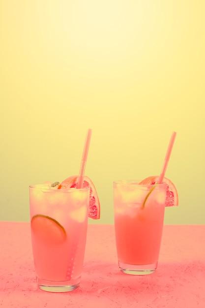 Frischer rosafarbener alkoholischer cocktail mit pampelmuse; zitronenscheibe und eiswürfel gegen gelben hintergrund Kostenlose Fotos