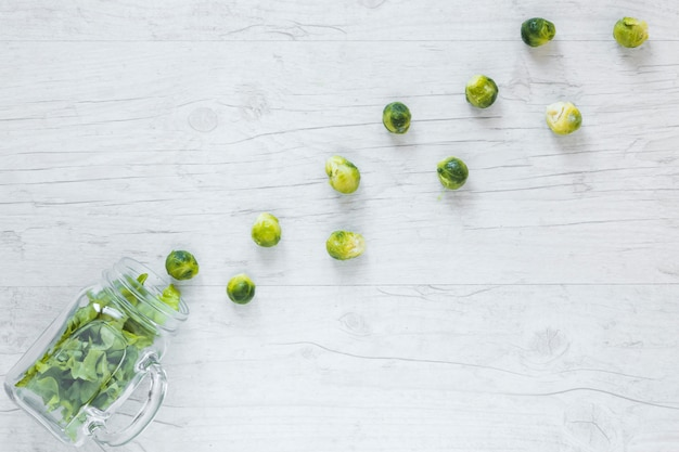 Frischer rosenkohl und kopfsalat vereinbarten mit glas auf hölzernem schreibtisch Kostenlose Fotos