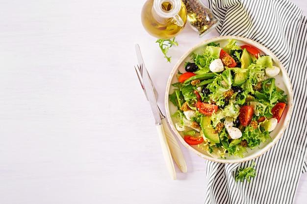 Frischer salat mit avocado, tomate, oliven und mozzarella in einer schüssel. Premium Fotos