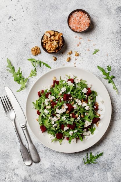 Frischer salat mit rucola, feta, walnuss und roter rübe auf weißer platte Premium Fotos
