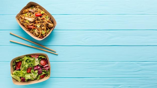 Frischer salat und chinesischer teller mit exemplarplatz Kostenlose Fotos