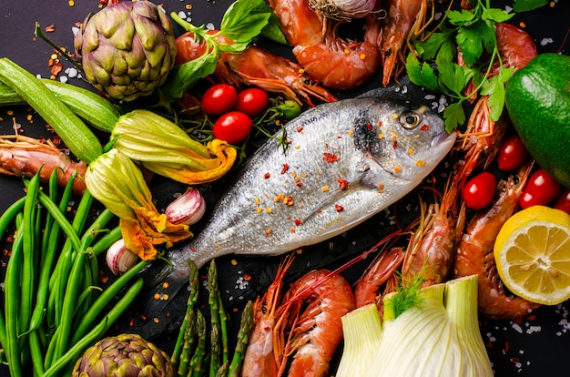 Frischer seebrassen- oder doradofisch und garnelen mit zutaten und gemüse zum kochen. Premium Fotos