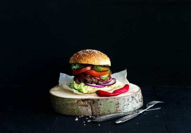 Frischer selbst gemachter burger auf hölzernem umhüllungsbrett mit würziger tomatensauce, seesalz und kräutern über schwarzem hintergrund. Premium Fotos