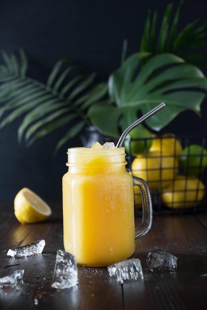 Frischer sommerfruchtsaft mit zitrone auf dunklem tropischem hintergrund. nahansicht. Premium Fotos