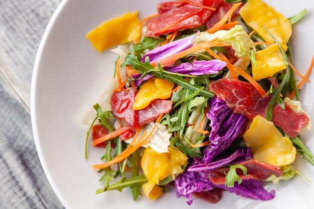 Frischer sommersalat der nahaufnahme mit bresaola-fleisch, grüns, rucola, mango, karotte, chinakohl. Premium Fotos