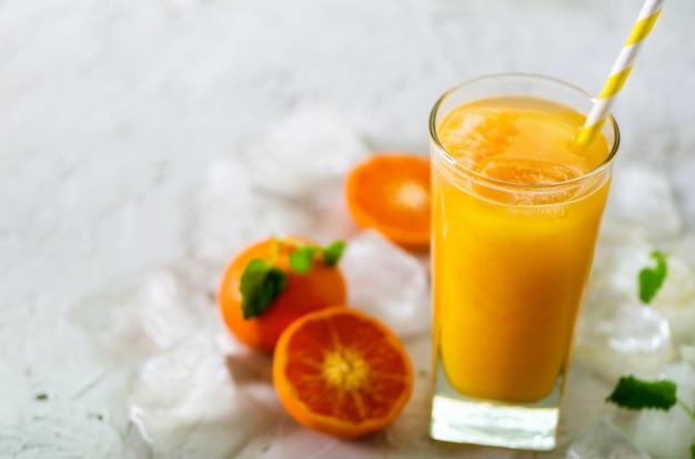 Frischer tangerinesaft im glas. orange früchte mit eis, minze. kaltes getränk für heiße sommertage. exemplar Premium Fotos