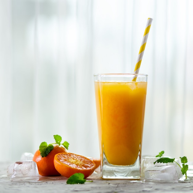 Frischer tangerinesaft im glas. orange früchte mit eis, minze. kaltes getränk für heiße sommertage. Premium Fotos