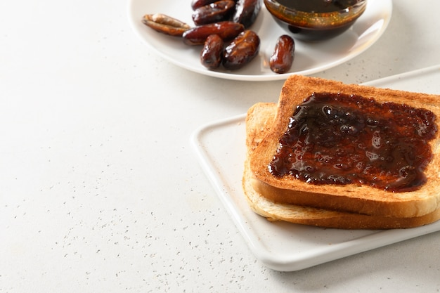 Frischer toast mit dattelmarmelade ohne zucker auf weißem tisch. nahansicht. speicherplatz kopieren. Premium Fotos