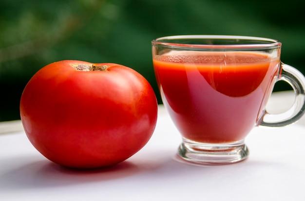 Frischer tomatensaft in der glasschale und in der tomatenfrucht, abschluss oben Premium Fotos
