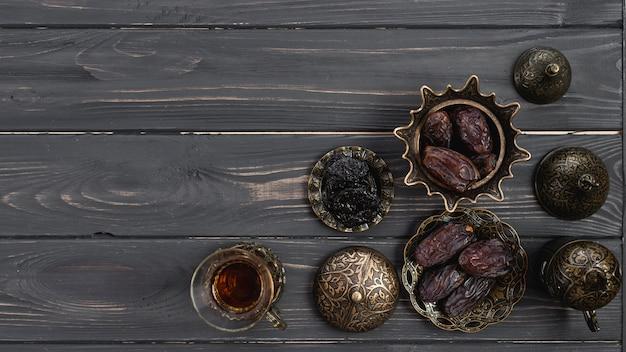 Frischer traditioneller tee und daten an der metallischen schüssel über dem hölzernen schreibtisch Kostenlose Fotos