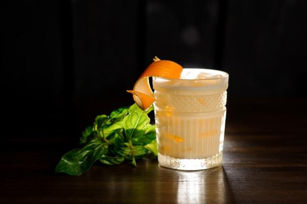 Frisches alkoholisches getränk in einem glas verziert mit orangenschale und basilikum Premium Fotos