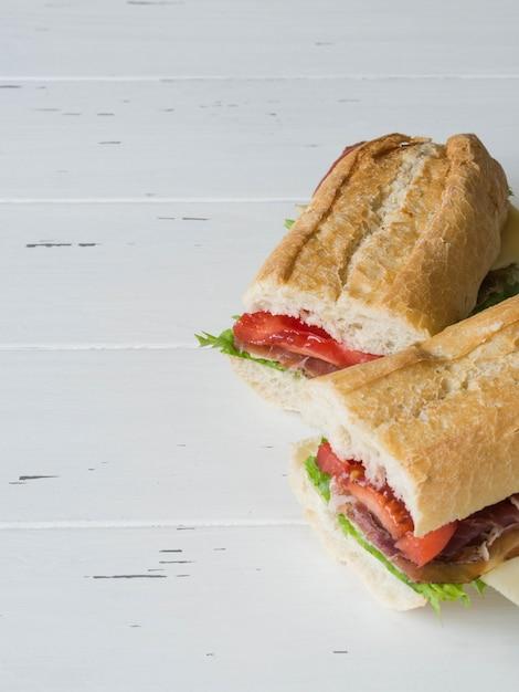 Frisches baguettesandwich mit fleisch, schnittkäse, tomaten und frischem kopfsalat Premium Fotos