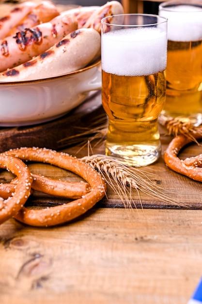 Frisches bier mit schaum auf einem hölzernen. oktoberfest deutsche brezeln. Premium Fotos