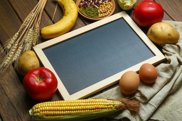 Frisches bio-gemüse, früchte, eier, bohnen und mais mit tafel auf vintage holztisch Kostenlose Fotos