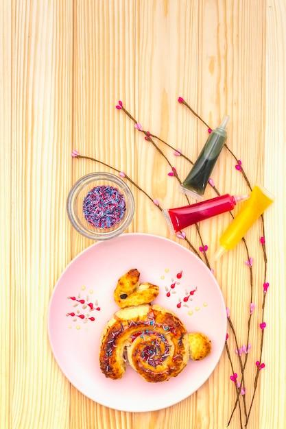 Frisches brötchen in form eines osterhasen. das konzept der kinderferienbäckerei. in der rosa keramischen platte mit künstlicher weide verzweigt sich auf holzoberfläche, draufsicht, abschluss oben. Premium Fotos