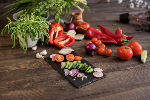 Frisches buntes gemüse von einem gemüsegarten auf einem dunklen hölzernen hintergrund Premium Fotos