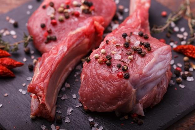 Frisches fleisch vom knochensteak mit gewürzen und kräutern Premium Fotos