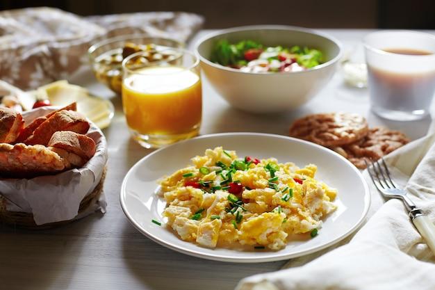 Frisches frühstück essen. rührei und orangensaft. Premium Fotos