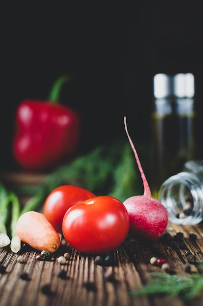 Frisches gemüse tomaten radieschen und karotten schließen auf einem hölzernen hintergrund Premium Fotos