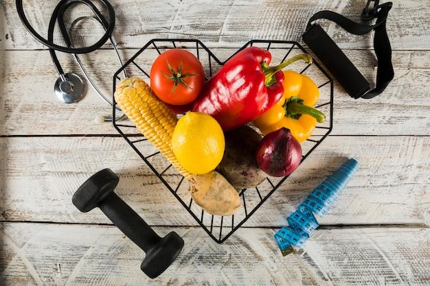 Frisches gemüse, umgeben von fitnessgeräten; stethoskop und maßband Kostenlose Fotos