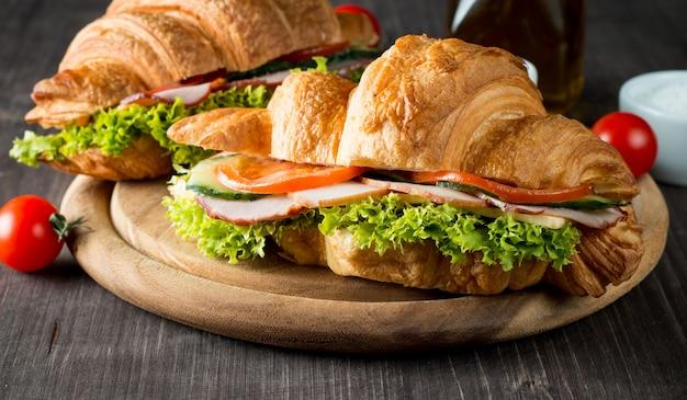Frisches hörnchen oder sandwich mit salat, schinken auf hölzernem hintergrund. Premium Fotos
