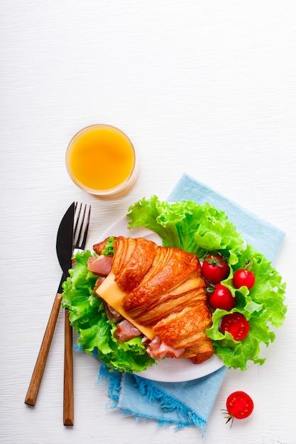 Frisches hörnchen-sandwich mit schinken, käse, kirschtomaten Premium Fotos