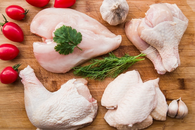 Frisches hühnerfleisch zum kochen mit tomaten und zutaten Kostenlose Fotos