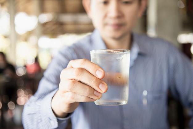 Frisches kaltes reines wasser des manngetränks im glas Kostenlose Fotos