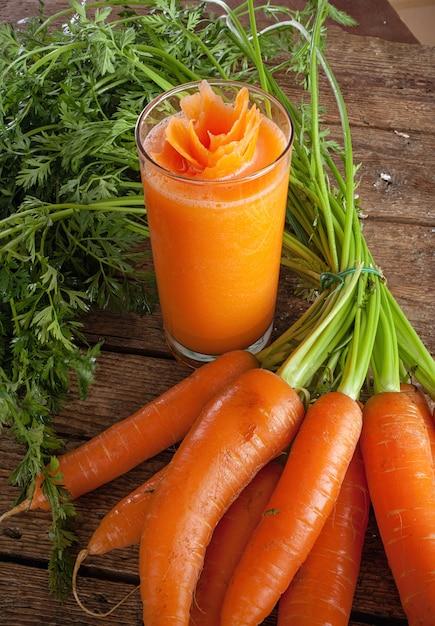 Frisches karottensaftglas mit frischen organischen karotten Premium Fotos