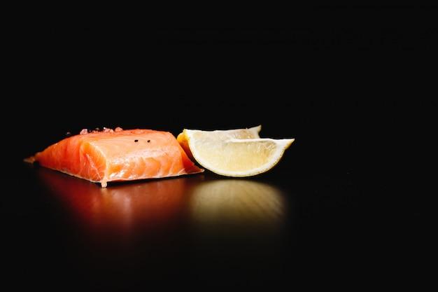 Frisches, leckeres und gesundes essen. rote lachse und zitrone auf schwarzem hintergrund isoliert Kostenlose Fotos