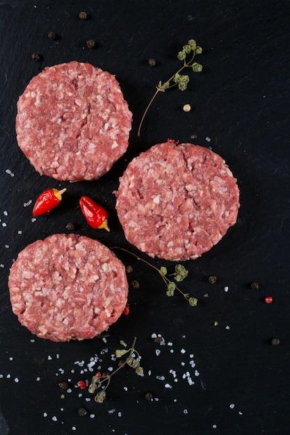 Frisches rohes fleisch burger schnitzel auf dem schwarzen schieferbrett mit kräutern und gewürzen. speicherplatz kopieren, draufsicht. selektiver fokus. Premium Fotos