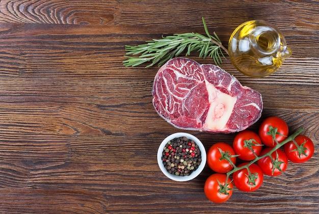 Frisches rohes fleisch-rindersteak mit knochen mit gewürzen rosmarin-tomaten und olivenöl Premium Fotos