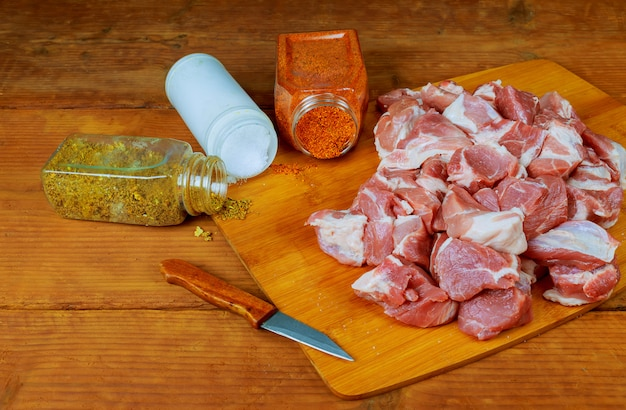 Frisches rohes gehacktes rindfleisch auf einem hölzernen schneidebrett mit gewürzen, kräutern und gemüse. Premium Fotos