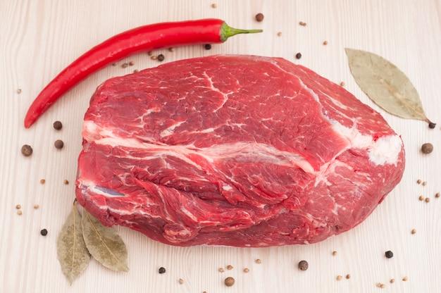 Frisches rohes rotes rindfleischfleisch mit gewürzen auf holztisch Premium Fotos