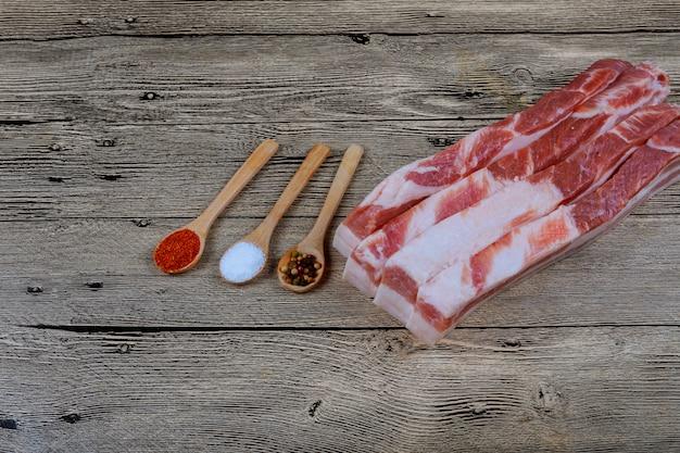 Frisches rohes schweinefett mit gewürzen für das in essig einlegen auf einem hölzernen brett des ausschnitts. Premium Fotos