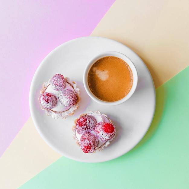 Frisches selbst gemachtes fruchttörtchen mit himbeer- und kaffeetasse auf platte Kostenlose Fotos