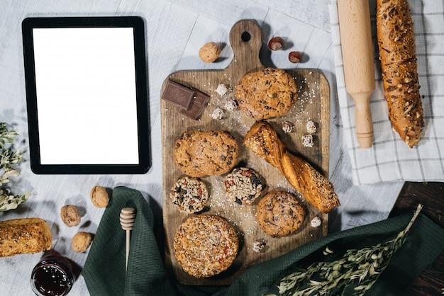 Frisches selbst gemachtes süßes gebäck mit tablette Premium Fotos