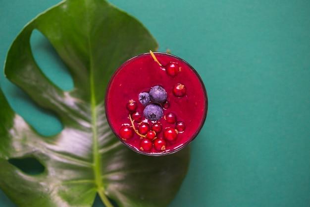 Frisches smoothieglas auf monstera-blatt über dem grünen hintergrund Kostenlose Fotos