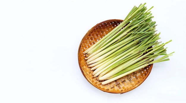 Frisches zitronengras im hölzernen bambusdreschkorb auf weißem hintergrund. Premium Fotos