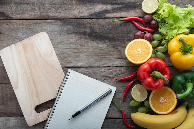 Frischgemüse und früchte für eignungsabendessen auf hölzernem hintergrund Premium Fotos