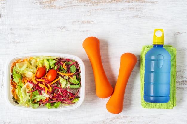 Frischgemüsesalat in der brotdose mit orange dummköpfen und energiewasser trinken auf weißem rostigem holz Premium Fotos