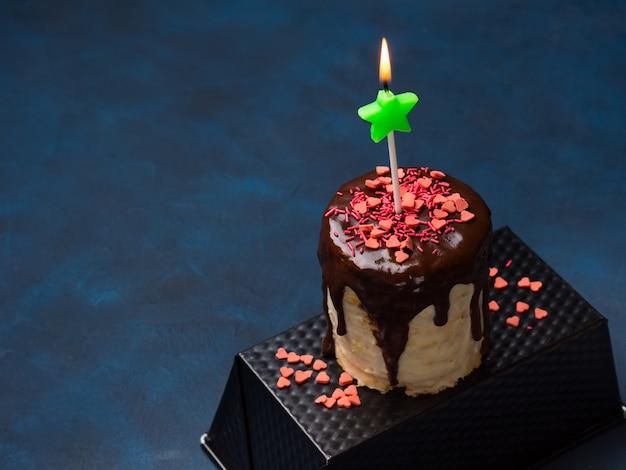 Frischkäse-biskuit mit schokoladenglasur und rosa herz besprüht auf dunkelblauem. geburtstagsfeier valentine muttertag behandeln Premium Fotos