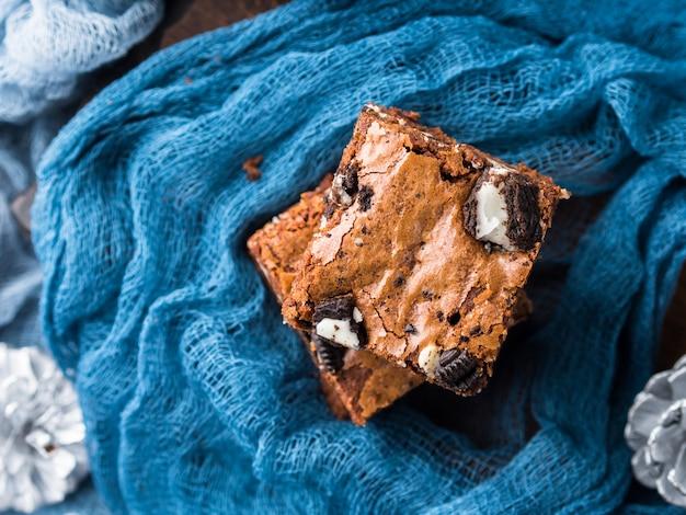 Frischkäseschokoladenkuchen mit plätzchen auf blau. quadratische schokoriegel der winterweihnachtsfestlichkeit. Premium Fotos
