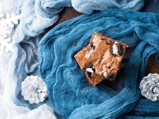 Frischkäseschokoladenkuchen mit plätzchen auf blau. winterweihnachtsfestlichkeitsquadrat-schokoriegel. Premium Fotos