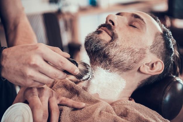 Friseur bürstet rasierschaum auf mans gesicht. Premium Fotos